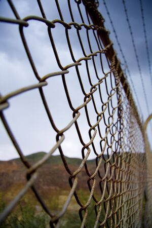 Tall chain link fencing in desert photo