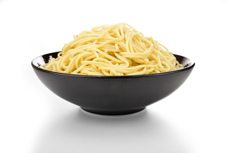 Black ceramic pasta bowl overflowing with noodles