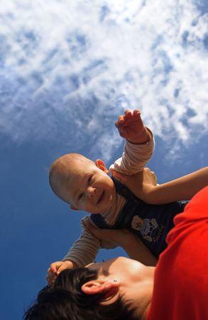 Baby and his mother are having outdoor fun together. The mother lifts him higher and higher and they are smiling a lot. Stock Photo - 427336