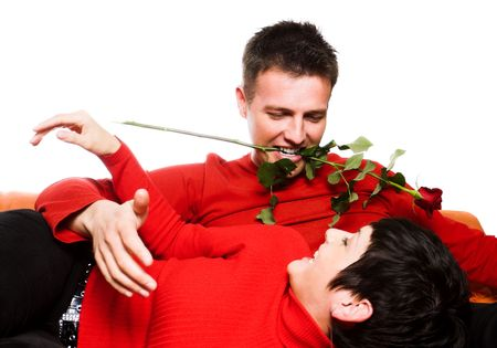 This is a happy moment. A young couple is having a date and the man tries to be very romantic and seductive. He keeps a rose between his teeth and the woman finds this very funny and she laughs. Stock Photo - 428201