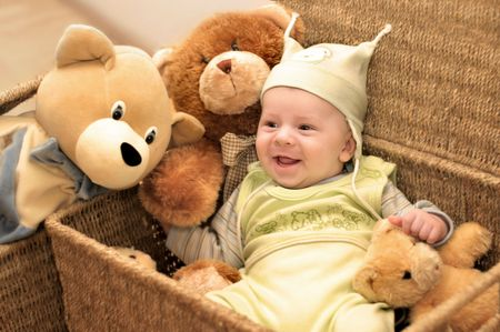 A baby and the group of teddy bears are sitting in backets. photo