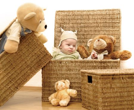 A baby and the group of teddy bears are sitting in backets.