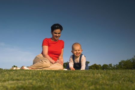Baby and his mother are having outdoor fun together and they are smiling a lot. There are nice afternoon lights. Stock Photo - 428156