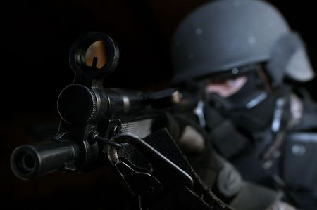 A guy wearing a tactical swat suit is aiming seriously by his submachinegun. Stock Photo