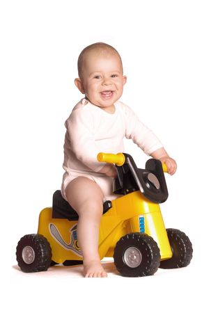 enjoys: 11 moths old baby rides a toy motorbike and he really enjoys it. Stock Photo