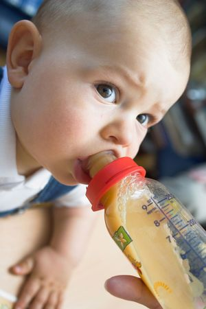 nursing bottle: A cute one year old baby is drinking from the nursing bottle while he is looking at her mother. The entire shot is soft, the DOF is very shallow, only the closest eye and the teat are sharp.