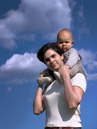 A one year old baby and his mom are spending some time together outdoor. The background is the clear blue sky. photo