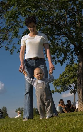 A one year old baby and his mom are spending some time together outdoor. The baby is precticing how to walk. photo