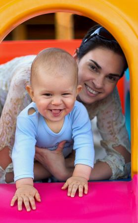 Baby and his mother are playing togather on a playground. Stock Photo - 474889
