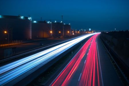 jamming: Heavy traffic on a highway. Due to the long exposure time the front and rear lamps of the cars are forimg a white and a red snake of light. There are huge storage tanks on the left side.