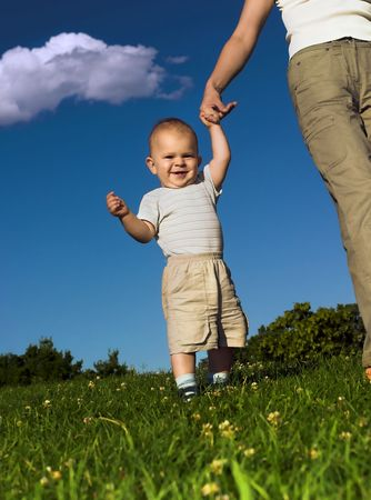 citypark: 1 year old  is practicing how to walk while his mother give him a helping hand. Stock Photo