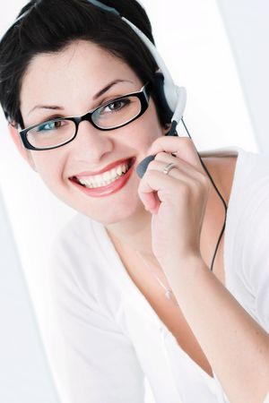 Beautiful young woman with charming big green eyes is bearing modern glasses and receiving calls on a headset. photo