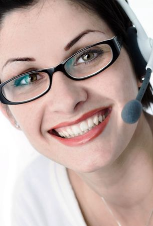 outwork: Beautiful young woman with charming big green eyes is bearing modern glasses and receiving calls on a headset.