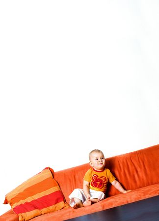 domesticity: Baby is sitting on the couch and there is a huge white background area above him, ideal for any written text.
