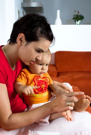 domesticity: One year old baby and his mother are sitting and resting together on a couch. The mother shows him something. It is a typical home enviroment.