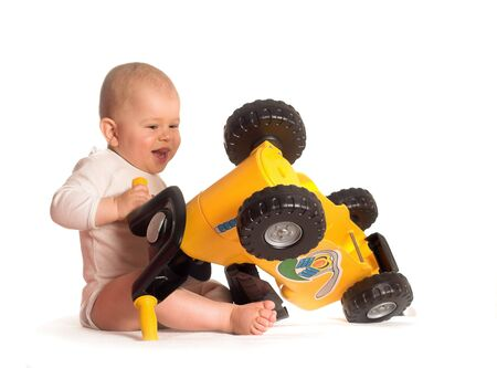11 moths old baby rigs out a toy motorbike and he really enjoys it. Stock Photo - 496381