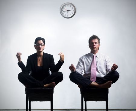 Young business people in an abstract office environment are sitting in yoga lotus-pose and relaxing. Stock Photo - 548601