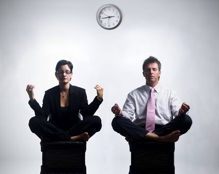 successfull: Young business people in an abstract office environment are sitting in yoga lotus-pose and relaxing. Stock Photo