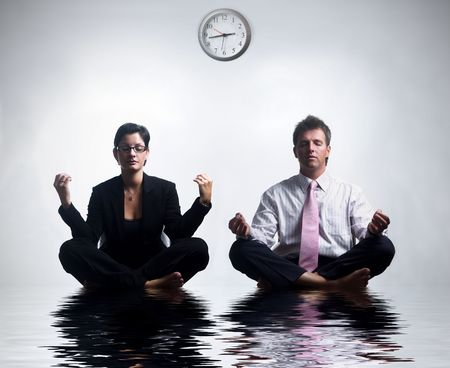 Young business people in an abstract office environment are sitting in yoga lotus-pose and relaxing. Stock Photo - 548599