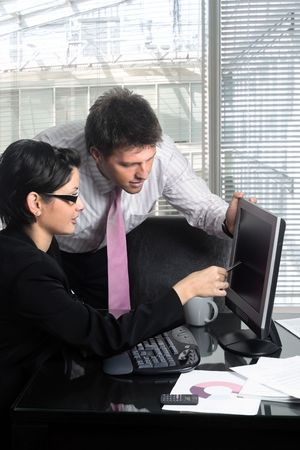 Young and good-looking business people are working tohether on a desktop computer in a modern office.