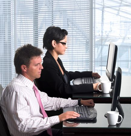 desktop computers: Young, good looking and well-dressed office workers are working on similar desktop computers in a modern office.