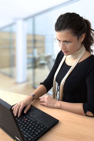 telework: Young businesswoman works on a laptop computer in the modern office. Stock Photo
