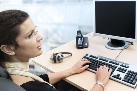 telecommuting: Young businesswoman works on a laptop computer in the modern office. Stock Photo