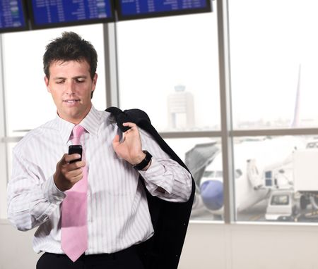successfull: Businessman is waiting for his flight on the airport. He is playing a game or dialing someone on his mobile. Stock Photo