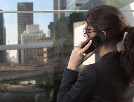 telecommuting: Young businesswoman talks on a mobile phone in her very exclusive office in the downtown.