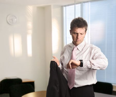 just in time: Young and handsome businessman checkes the time on his watch while just arrived or leaving. Stock Photo