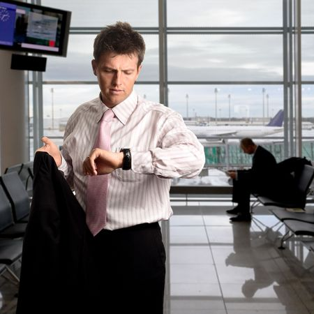 successfull: Young Businessman is waiting in the airport waiting hal and he checks the time on his watch. Stock Photo