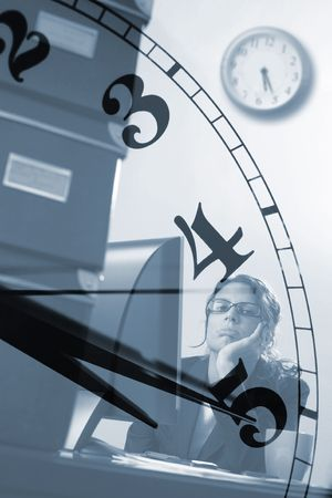 officeworker: Bored young female officeworker thinks of the time when business hours end.