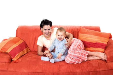 domesticity: Baby and mother are playing together on the sofa. They are wearing pijamas.