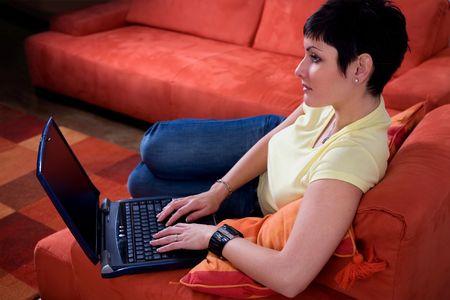 outwork: Joven mujer est� usando un ordenador port�til es su c�moda sala de estar.