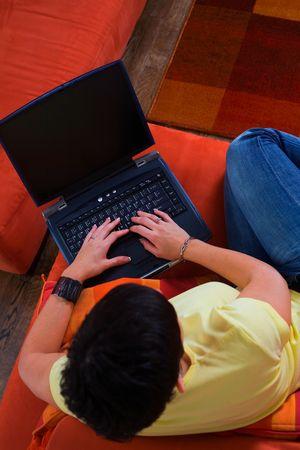 outwork: La mujer joven es que se sienta y de reclinaci�n sobre el sof� y con una computadora de computadora port�til. Ella est� practicando surf la red, est� charlando o studing quiz� para el examen siguiente de la universidad.