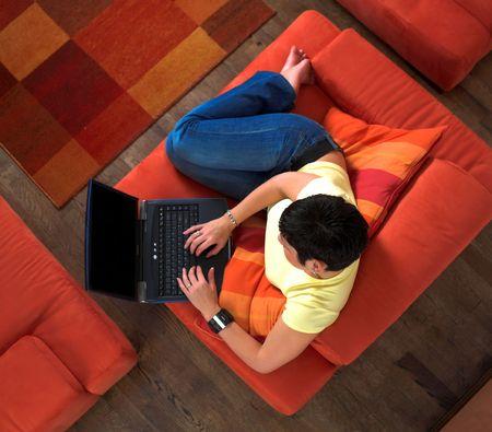 net surfing: Giovane donna � seduta e di riposo sul divano e utilizzo di un computer portatile. Forse lei � navigare in rete, chat o di studio per il prossimo esame universitario.