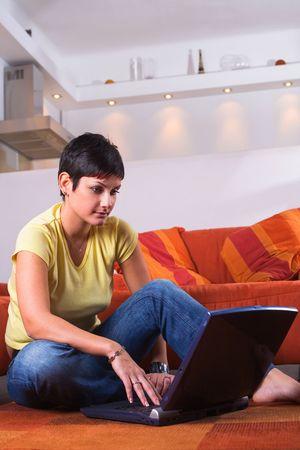 outwork: La mujer joven se est� sentando en el piso y est� utilizando una computadora de computadora port�til. Ella est� practicando surf la red, est� charlando o studing quiz� para el examen siguiente de la universidad. Foto de archivo