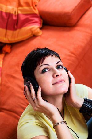 listening to music: La mujer joven es m�sica que escucha en un auricular en el livingroom.