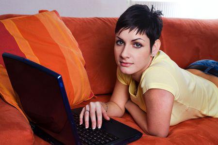 outwork: La mujer joven est� utilizando una computadora de computadora port�til es su sitio vivo c�modo. Foto de archivo