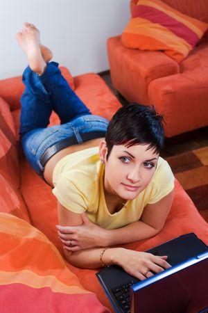 outwork: Joven mujer est� mintiendo y descansando en el sof� y utiliza un ordenador port�til. Tal vez ella est� navegando por la red, chatear o estudiar para el pr�ximo examen de la universidad.  Foto de archivo
