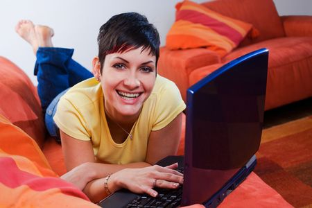 outwork: Young woman is using a laptop computer is her comfortable living room. Stock Photo