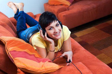 listening to music: Mujer joven est� escuchando m�sica con un auricular en la sala.