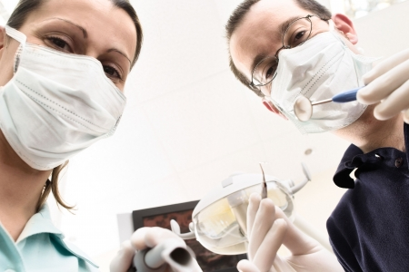 Dentist and assistant are examining you the patient photo