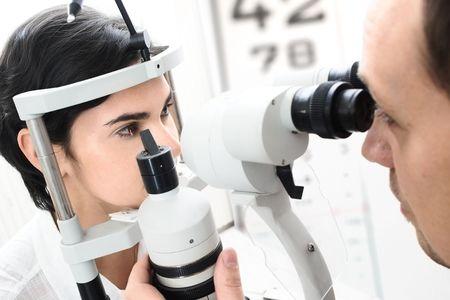 El paciente femenino joven hermoso está teniendo una atención médica en el optómetra.