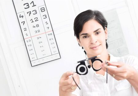 diopter: Young female optometrist with an universal messbrille in hand.