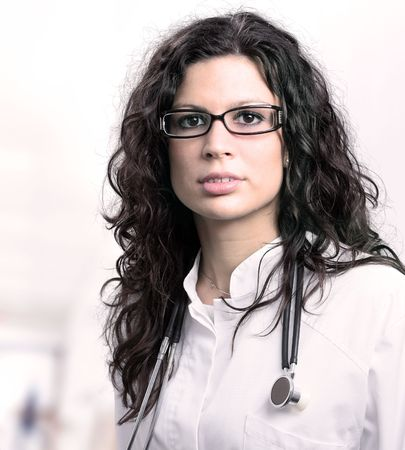 medical attendance: Portrait of a beautiful young female doctor, taken on the hospital corridor.