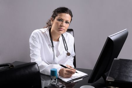 inoculation: Young female doctor works on her desk.