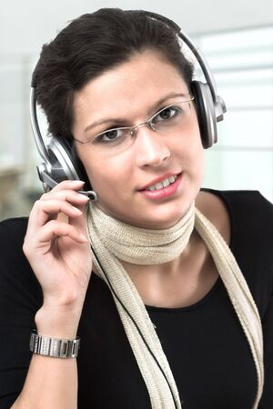Young brunette operator recieves calls on a headset. Stock Photo - 841451