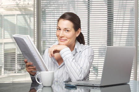 successfull: Young businesswomen reads a printed document.