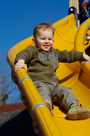 Young boy is playing outdoor and enjoys the speed on the slide-way. Stock Photo